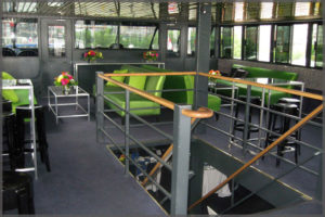 Cruise decor with bright green settees and black bar stools.