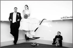 Black and white picture of bride, groom and ring bearer on the bow of the ship.