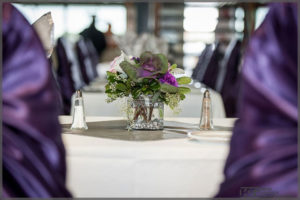 Wedding decor with mauve chair covers and matching floral centrepiece.
