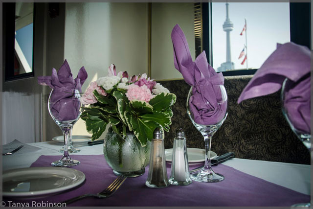 Wedding centrepiece of pink and white flowers with mauve napkins and wine glasses.