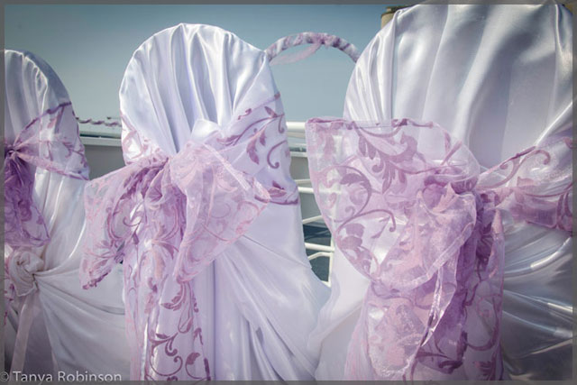 White chair covers with mauve bows make this wedding decor simple but elegant.
