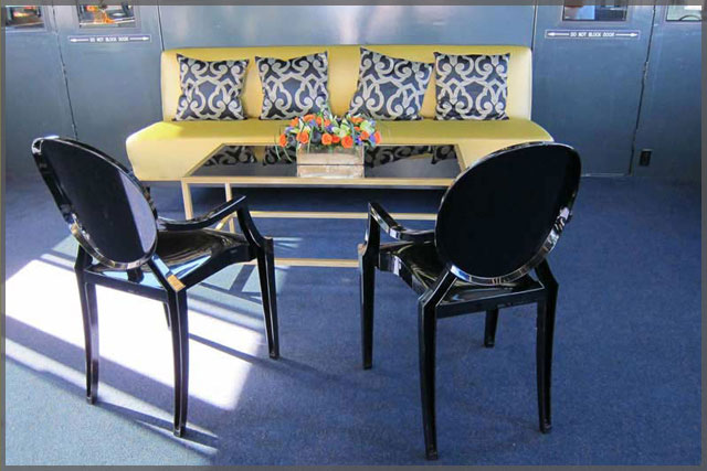 Sitting area for a corporate cruise with yellow settee and 2 black chairs.