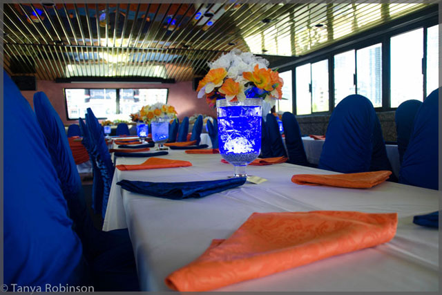 Floral centrepiece with white and orange flowers. Blue and orange napkins with blue chair covers.
