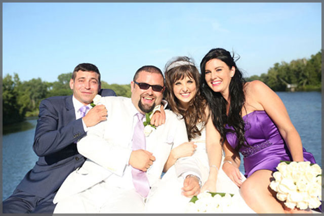Bride and groom celebrate their wedding with the best man and bridesmaid on their wedding cruise.