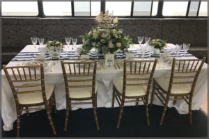 Table set up Nautical decor dinner cruise with white roses and gold chairs.