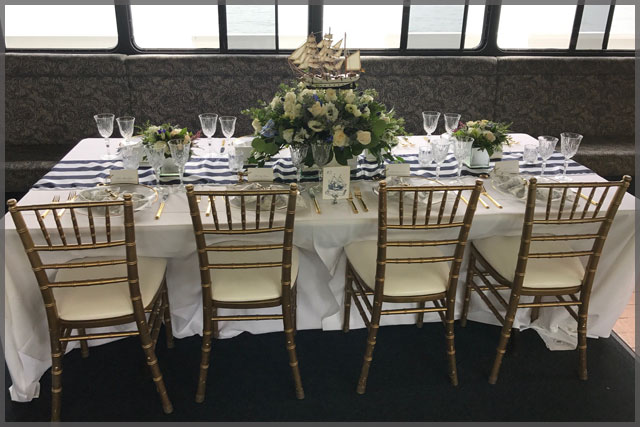 Table set up for Nautical decor dinner cruise with white roses and gold chairs.