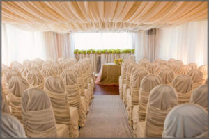 Sultans tent wedding decor with chair covers and ceiling drapes.