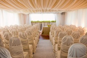Sultans tent wedding decor with chair covers and drapery.