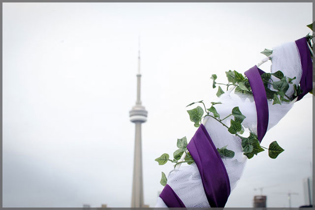 Wedding arch with mauve ribbon and ivy decor and CN Tower in the background.