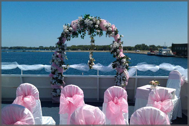 Wedding arch and chairs decorated with pink decor, white flowers and ivy.