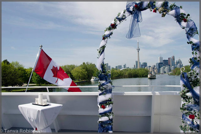 Wedding arch wrapped with blue and white tulle and the Toronto CN Tower in the background.