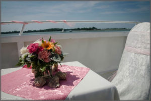 Wedding registration table with centrepiece pink flowers surrounded by sea shells.