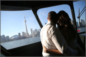 Couple enjoying the view of the CN Tower and Toronto skyline from the wheelhouse of a cruise boat.