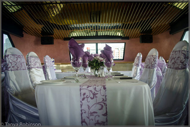 Wedding decor with mauve accents on chairs, table runners and napkins.