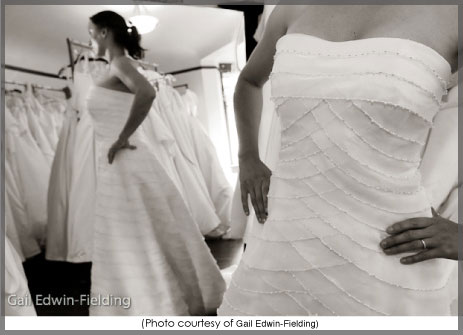 Bride trying on a wedding dress in front of a mirror.
