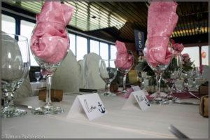 Wine glasses with pink wedding decor.