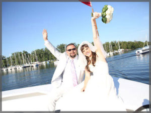Bride and groom celebrating their wedding on the bow of the boat.