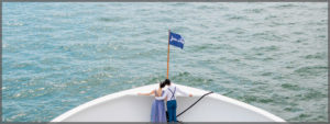 Bride and groom standing on the bow of one of our magnificent cruise ships .