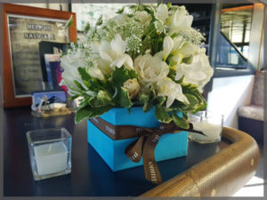 Floral centrepiece with white accent flowers for wedding cruise.