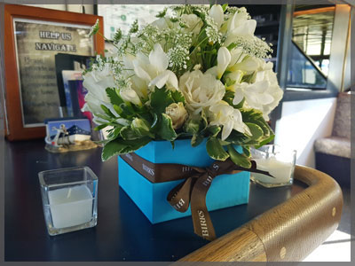 Centrepiece with white flowers in a blue square vase for a corporate cruise.