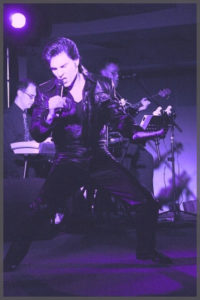 Elvis impersonator James Begley doing his thing in purple overlay of image.