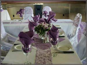 Table centrepiece with mauve napkins in wine glasses for a wedding cruise.