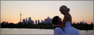 Bride and groom hugging with the Toronto skyline in the background at sunset.