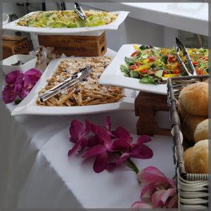 Buffet items of pasta, caesar salad and mixed house salad.