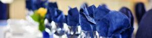 Blue napkins in wine glasses.