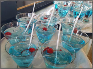 Blue martinis with maraschino cherry.