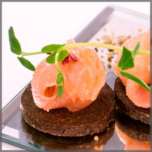 Hor D'oeuvres of salmon on a round pumpernickel wafer.