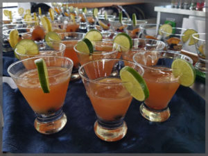 Fruit drinks lined up with slice of lime.