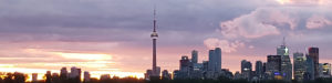 Toronto skyline at sunset with CN Tower in the middle.