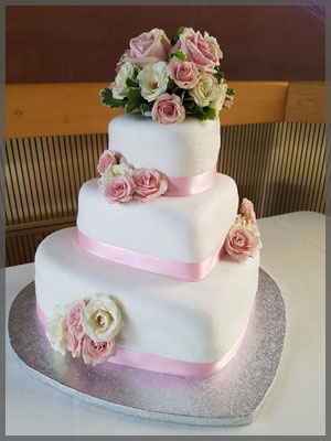 Wedding cakes with pink and white roses on three tiers.