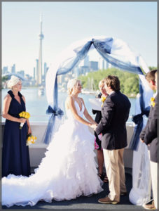"""Bride and groom say """"I Do"""" in wedding ceremony on the stern of the ship."""