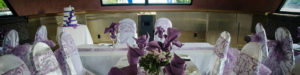Wedding decor with white chair covers and lavender napkins and bows.
