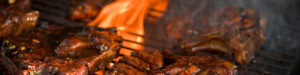 Steaks grilling over a bed of coals.