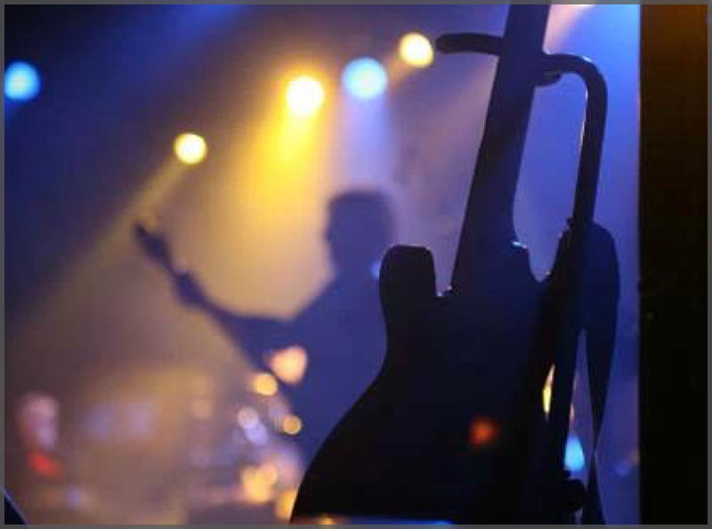 Live bands silhouette with guy playing guitar and electric guitar in the front right of the image.