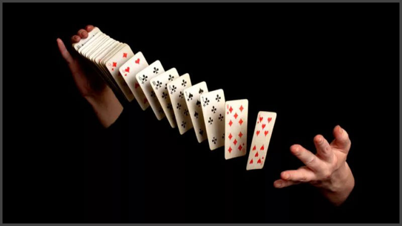 Magician shuffling a deck of cards with his body blacked out.